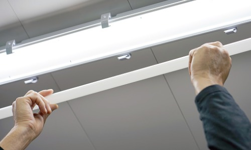 An electrical contractor putting in new lights as a part of Lighting Installation in Peoria IL