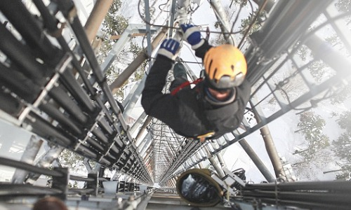 Commercial Electricians in Peoria IL performing service on a transmission tower